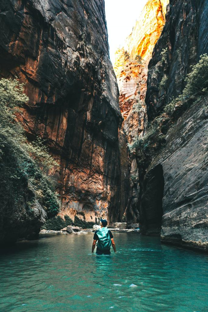 Man with a waterproof backpack strolling in waste-deep water through a narrow canyon heading to Havasu Falls admiring the sharp rising cliffs