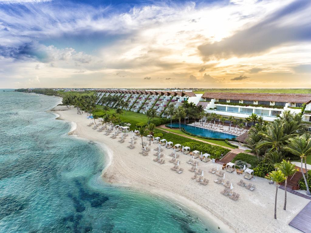 aerial view of the hotel along the white sand beach and turquoise water with green lawns and palm tress