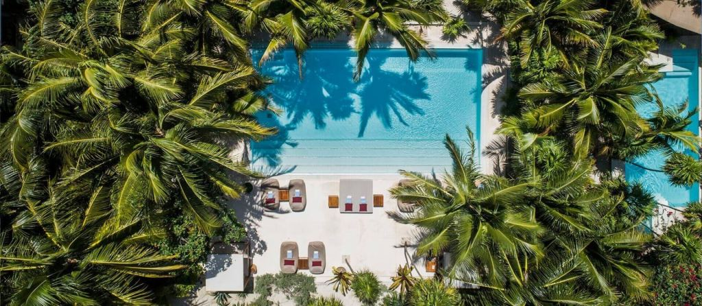 aerial view of hotel with pool and palm trees