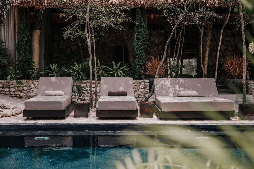 calm pool in the forefront with contemporary lounge chairs and couches and stone structures and topical plants in the background