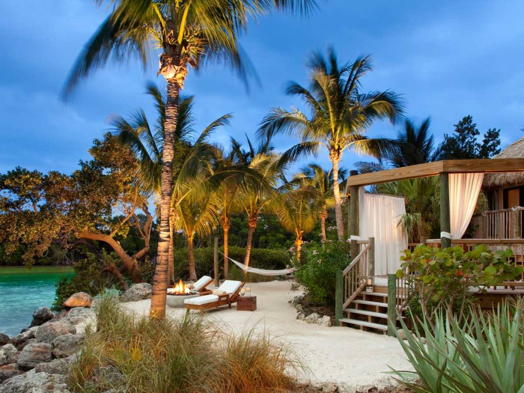 thatch hut-style private accommodation with palm trees lounge chairs and fire pit in front of a pool