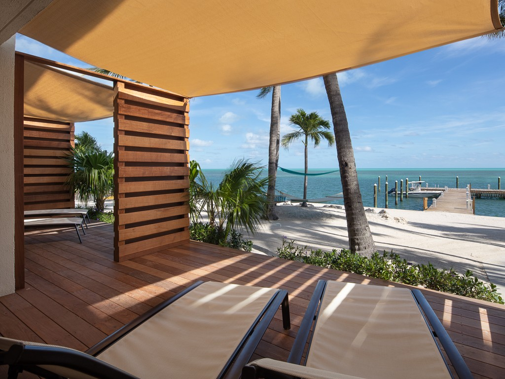 lounge chair deck overlooking the beach with palm trees and hammocks