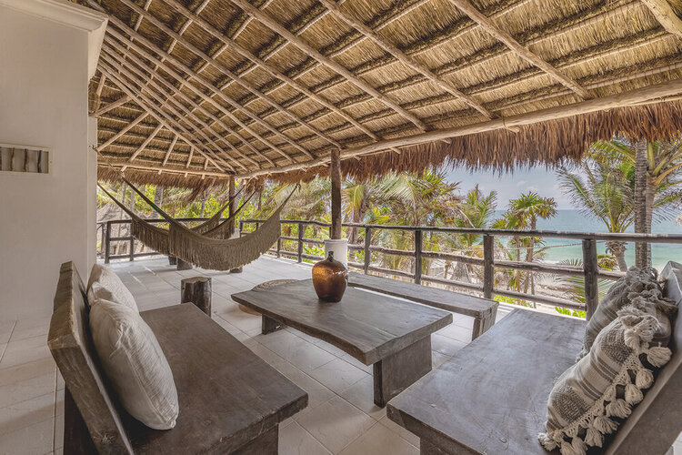 thatch roof hotel with natural wooden furniture overlooking the beach with palm trees