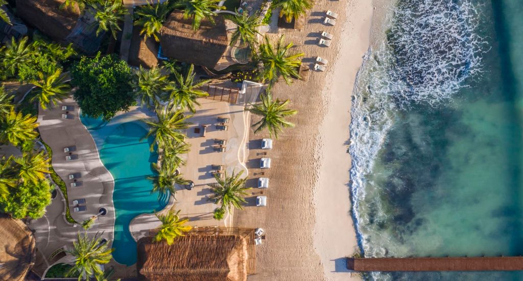 aerial view of the hotel along the beach and turquoise sea with green lawns and palm tress and pool