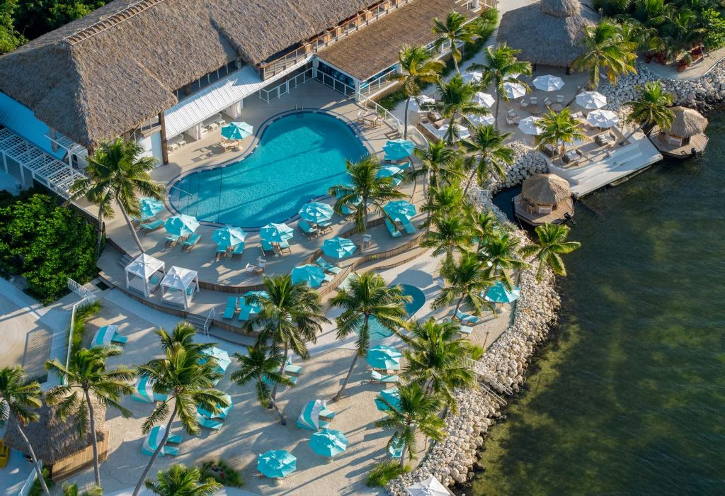 aerial view of a tropical island resort on the oceanfront with pool and dotted with light blue umbrellas providing shade to lounge chairs