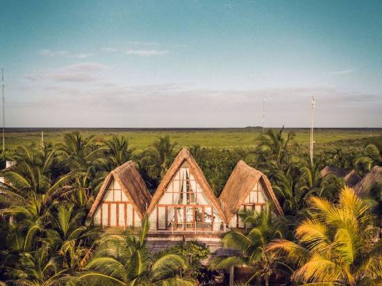 aerial view of hotel with three thatched villa roofs embedded in a tropical jungle