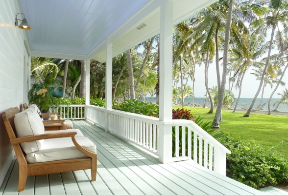 cottage porch deck with lounge chairs overlooking a green lawn, flowers, palm trees, and the ocean