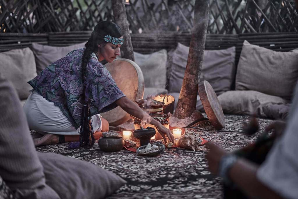 woman in native dress preparing an candles to perform an ancient healing treatment or ceremony