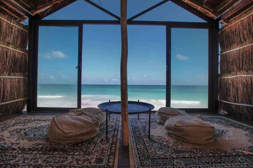 thatched roof hut with pillows and carpet looking right in front of a white sand beach with blue water