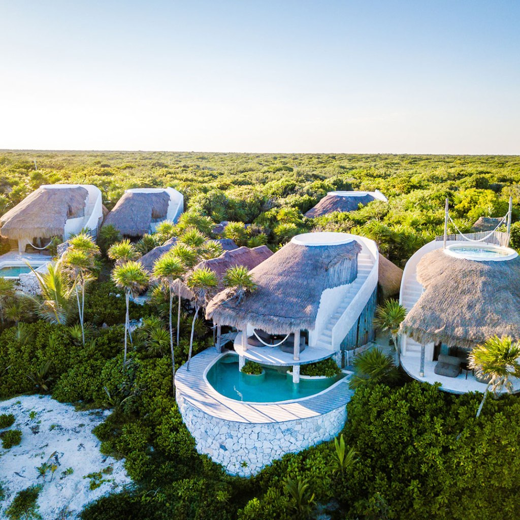 unique ancient-inspired hotel villas with modern construction dotting the jungle landscape