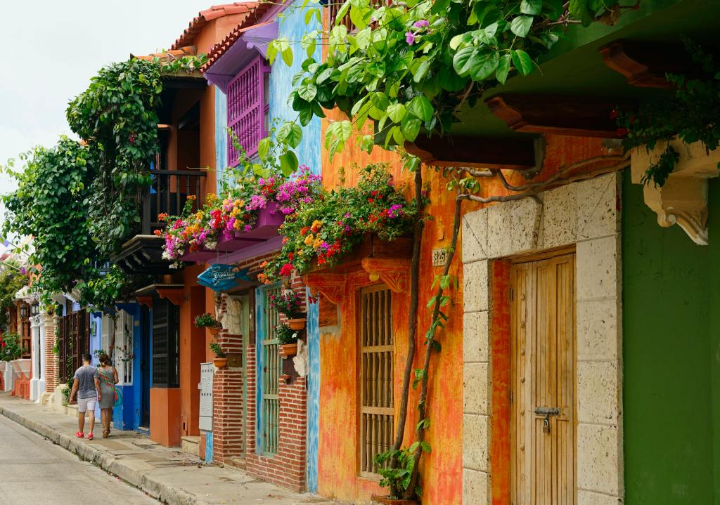 Colorful row of houses brightly painted with flowers overhanging outside of windows on a Colombian street