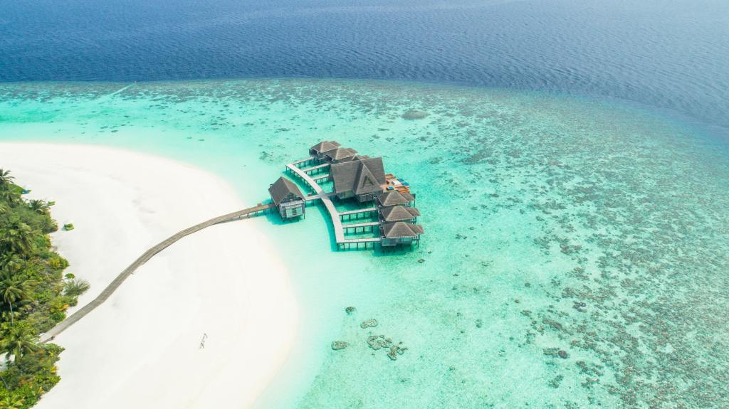 Aerial view of white sand and light blue water with bungalow style hotel rooms seemingly floating over the water