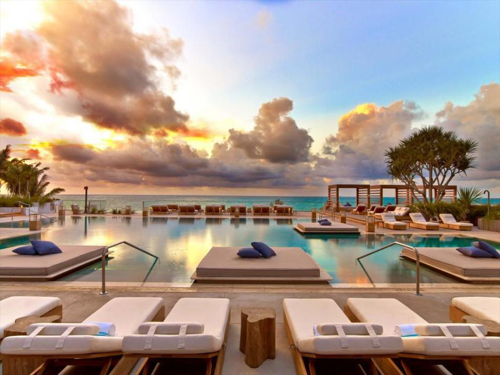 luxury white lounge chairs and cabanas with pool in background