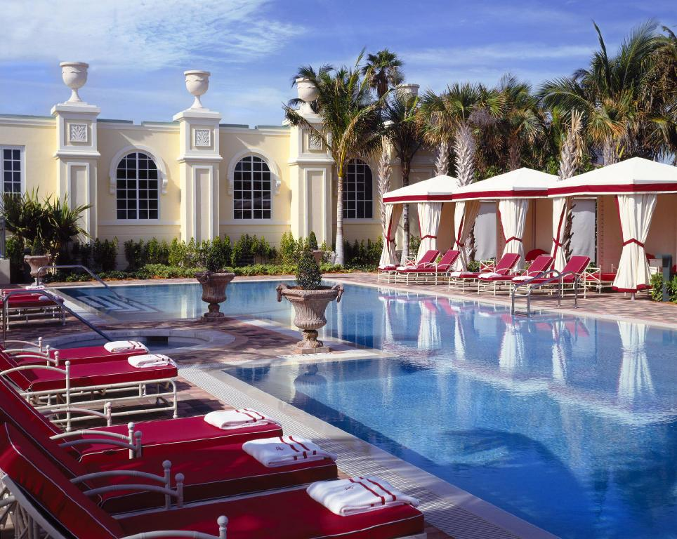 red lounge chairs with white towels surrounding clear blue pool with building facade in background