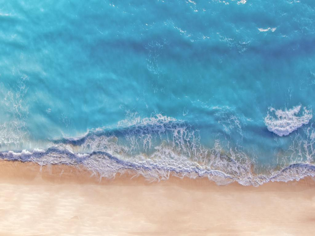 Aerial view of turquoise blue water washing into the white sand beaches of Cancun, Mexico