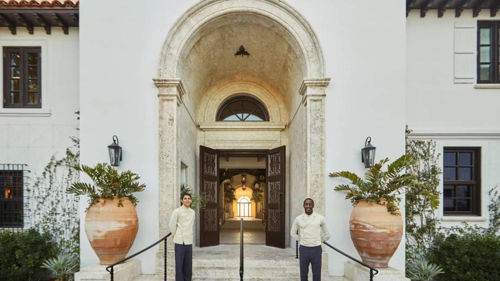entrance with two bellman in front of a luxurious and classic hotel doorway with large plants inside of exquisite pottery on the sides