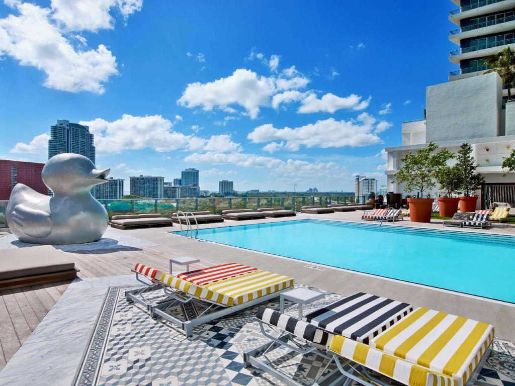 rooftop pool with city view in the background and colored lounge chairs in the foreground