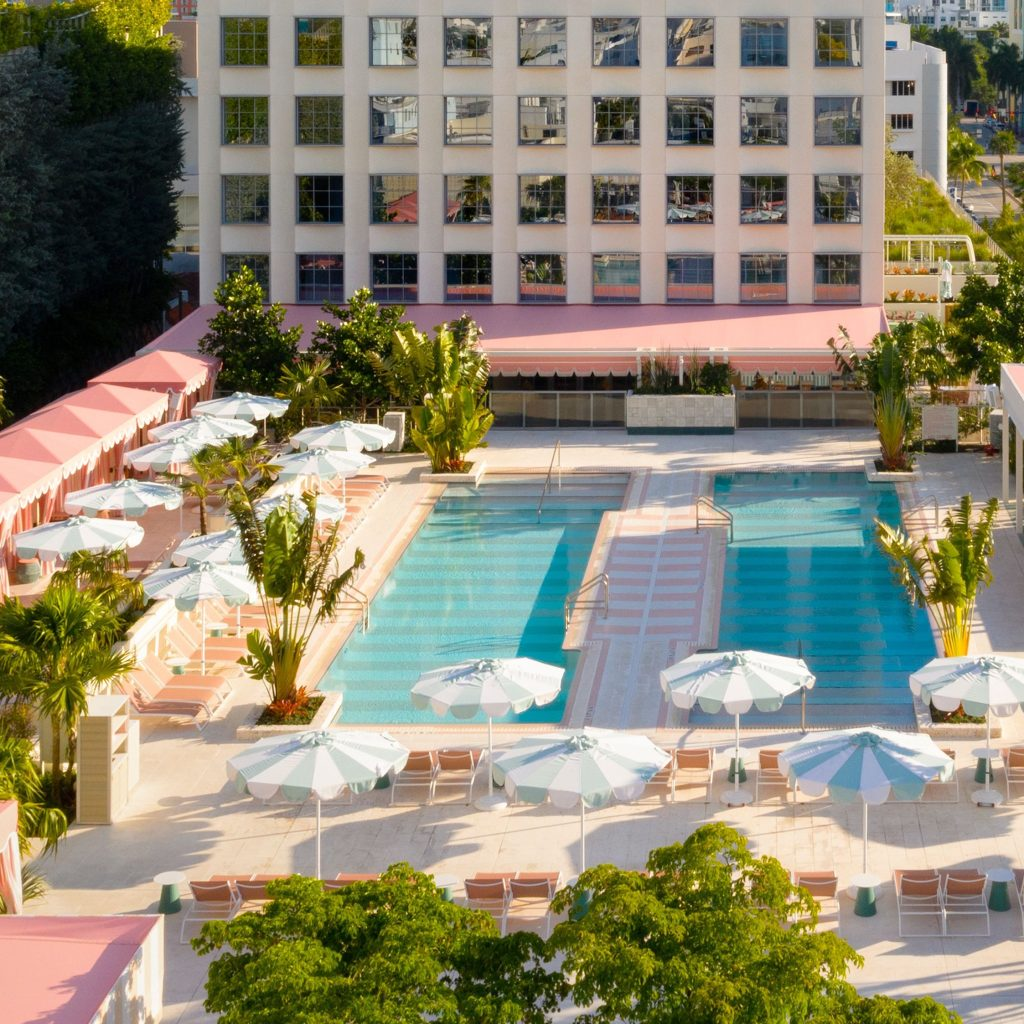 aerial view of two outdoor pools with pink rooftop cabanas