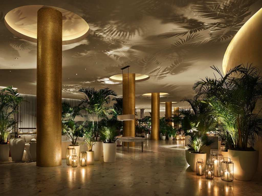 lobby interior with golden columns, tall ceilings, and soft white candle lighting around large green plants