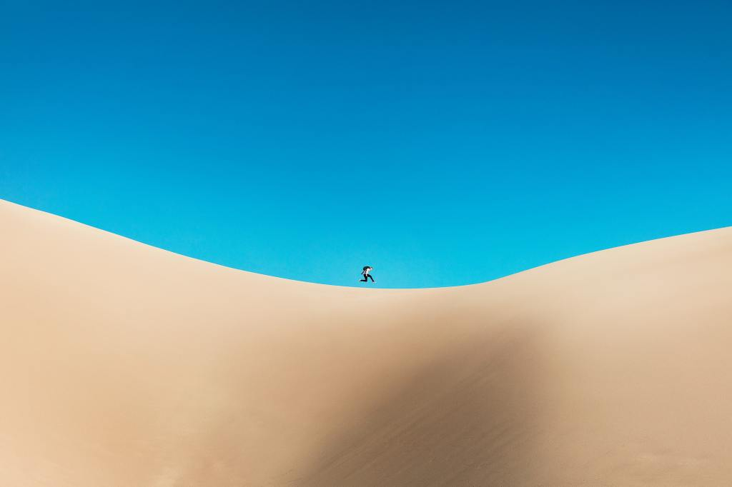 sand dunes with blue sky and person jumping on top of the dune ridge